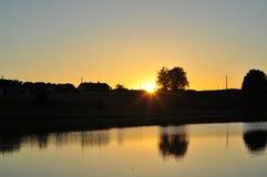 Solnedgång på en sjö i Frankrike med en lantgård Arkivbild