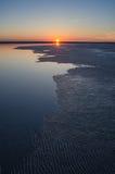 Solnedgång på en sjö med en ojämn kustlinje Fotografering för Bildbyråer
