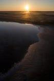 Solnedgång på en sjö med en ojämn kustlinje Royaltyfria Bilder