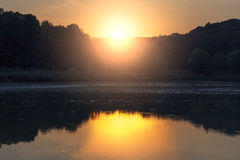 Solnedgång på en sjö nära skogen Fotografering för Bildbyråer