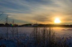 Solnedgång på en snöig lantgård royaltyfri bild