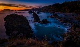 Solnedgång på en stenig strand Royaltyfri Foto