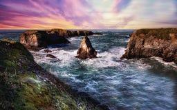 Solnedgång på en stenig strand Arkivbild