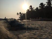 Solnedgång på en strand i norr Goa arkivbild