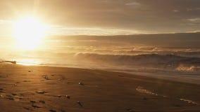 Solnedgång på en strand med bränning