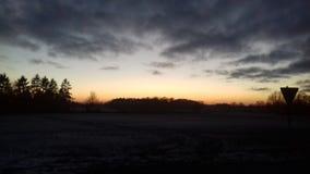 Solnedgång på ett fält med ett trafiktecken arkivfoton