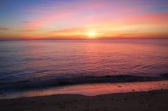 Solnedgång på ett plant hav Royaltyfria Bilder