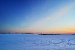 Solnedgång på ett snöig fält Arkivbilder