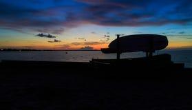Solnedgång på fjärden med kanoter och kajaker som konturer i sommar royaltyfria bilder