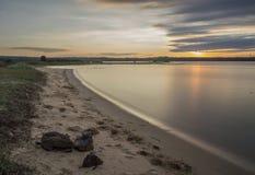 Solnedgång på fjärden med slätt vatten Arkivbild