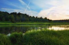 Solnedgång på flodbanken i sommarafton Arkivfoton