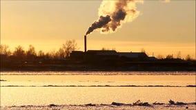 Solnedgång på floden Severnaya Dvina i vinter under frysning-upp Lastfartyget med kranar står på floden Severnaya Dvina, Ryssland lager videofilmer