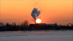 Solnedgång på floden Severnaya Dvina i vinter under frysning-upp på bakgrunden av ett industriellt ånga rör arkivfilmer