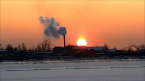 Solnedgång på floden Severnaya Dvina i vinter under frysning-upp på bakgrunden av ett industriellt ånga rör lager videofilmer
