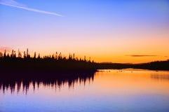 Solnedgång på floden Umba Liggande med en sten i vattnet royaltyfria bilder