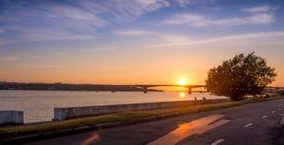 Solnedgång på flodkust med cyklar Royaltyfri Fotografi