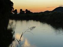 Solnedgång på flodlandskapet Royaltyfri Bild