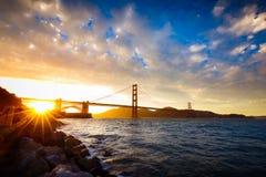 Solnedgång på Golden gate bridge med solstarburst Arkivfoto