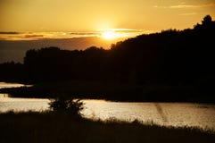 Solnedgång på gränsen av sjön Royaltyfri Bild