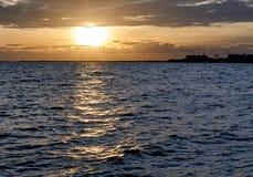 Solnedgång på havet med fabriken i bakgrunden arkivbild
