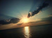 Solnedgång på havet och vingar formade moln Royaltyfria Foton