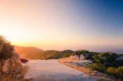 Solnedgång på kulleöverkant på den grekiska ön Lefkada Arkivbild