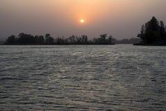 Solnedgång på kusten av floden i sommar Royaltyfria Foton