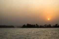 Solnedgång på kusten av floden i sommar Arkivfoton