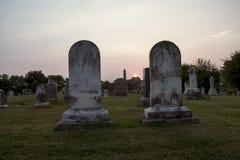 Solnedgång på kyrkogården med dubbla gravstenar Arkivbild