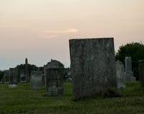 Solnedgång på kyrkogården med gravstenen Royaltyfri Foto