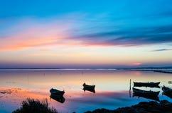 Solnedgång på lagun med fiskarefartyg Arkivfoton