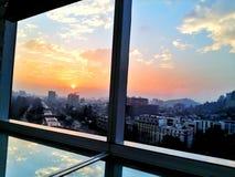 Solnedgång på office&en x27; s-fönster Royaltyfri Fotografi