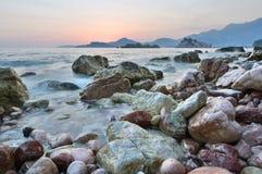 Solnedgång på Pebblet Beach Crvena Glavica budva riviera Montenegro arkivbilder
