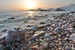 Solnedgång på Pebblet Beach Crvena Glavica budva riviera Montenegro royaltyfria bilder