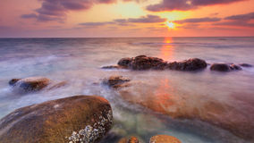 Solnedgång på Rock stranden Royaltyfri Foto