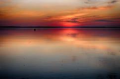 Solnedgång på sjön i sommar Royaltyfria Bilder