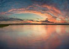 Solnedgång på sjön i sommartid Fotografering för Bildbyråer
