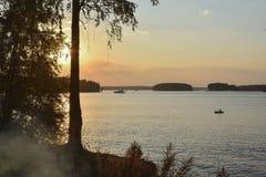 Solnedgång på sjön, kontur av björken royaltyfria foton