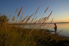 Solnedgång på sjön med att gå för kvinna Royaltyfria Foton