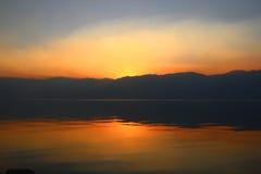 Solnedgång på sjöreflexion Arkivbild