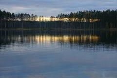 Solnedgång på skoglaken royaltyfria foton
