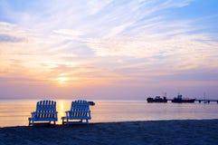 Solnedgång på stolar och fartyg för vardagsrum för picknickmittstrand i distan Arkivbilder