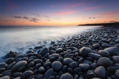 Solnedgång på stonebeachen Arkivfoto