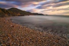 Solnedgång på stranden av kiselstenar Arkivfoton