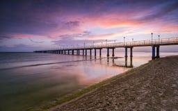 Solnedgång på stranden efter en storm, pir och i aftonen Royaltyfria Bilder