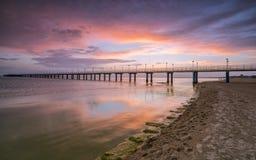 Solnedgång på stranden efter en storm, pir och i aftonen Arkivfoto