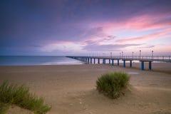 Solnedgång på stranden efter en storm, pir och i aftonen Arkivbild
