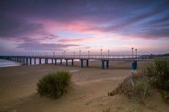 Solnedgång på stranden efter en storm, pir och i aftonen Royaltyfri Bild