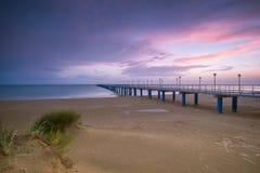 Solnedgång på stranden efter en storm, pir och i aftonen Fotografering för Bildbyråer