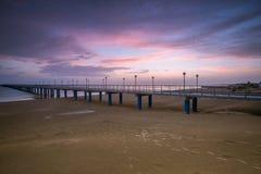 Solnedgång på stranden efter en storm, pir och i aftonen Arkivfoton